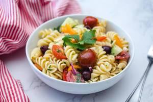 Italienischer Pasta-Salat mit Tomaten, Zwiebeln, Oliven und Gemüse in weißer Schale auf Tisch