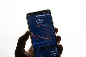 Jahresverlauf des Marktwertes von Ethereum (ETH) am Aktienmarkt auf Bildschirm von Smartphone