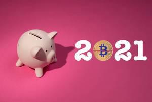 Jahreszahl 2021 mit Bitcoinmünze, auf pinker Hintergrund, neben einem rosa Sparschwein