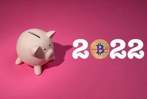 Jahreszahl 2022 mit Bitcoinmünze, auf pinker Hintergrund, neben einem rosa Sparschwein