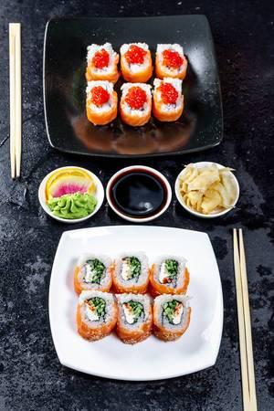 Japanischer Abendessen mit zwei Sushi-Teller, Wasabi, Sojasoße und Ingwer auf schwarzem Tisch