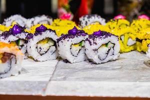 Japanisches Sushi in gelb und weiß mit lila Topping