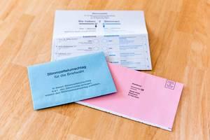 Jede Stimme zählt: Stimmzettel und Briefwahlunterlagen auf einem Holztisch