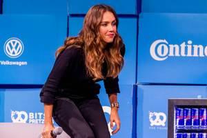 Jessica Alba setzt sich auf der Bits & Pretzels Bühne auf das Sofa