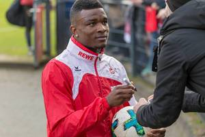 Jhon Córdoba signiert einen Ball