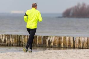 Joggender Mann mit gelber Trainingsjacke am Strand, mit dem Süßwassersee IJsselmeer bei Makkum im Hintergrund