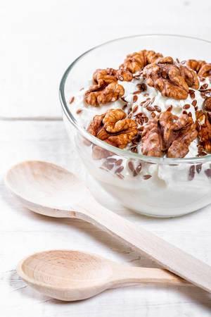 Joghurt-Quark Dessert mir Walnüssen und Holzlöffel auf weißem Holztisch