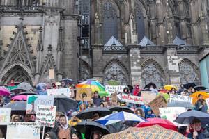 Jugendliche mit bunten Schilden für Umweltschutz vor dem Kölner Dom