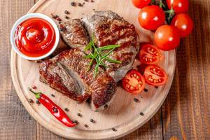 Juicy beef steak grilled on a kitchen Board with vegetables and spices