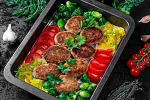 Juicy delicious meat cutlets with vegetables on a dark table in a rustic style
