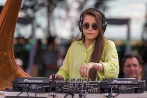 Junge DJane Kopfhörern am Mischpult legt am Tomorrowland Festival 2019 auf