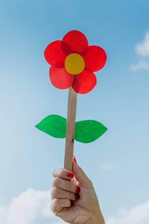 Junge Frau hält eine rote Papierblume in der Hand