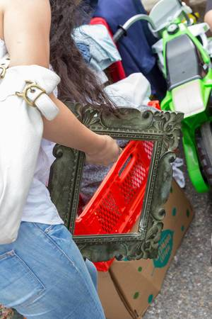 Junge Frau hält einen gebrauchten Bilderrahmen in der Hand
