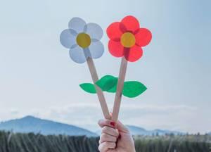 Junge Frau hält Papierblumen in der Hand