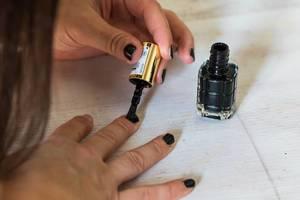 Junge Frau lackiert ihre Nägel mit schwarzem Nagellack