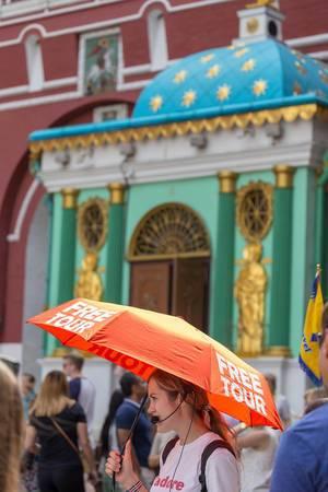 Junge Frau mit einem Regenschirm in der Hand mit der Aufschrift Free Tour
