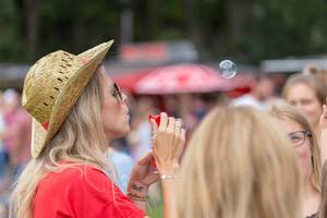 Junge Frau mit geflochtenem Hut macht Seifenblasen