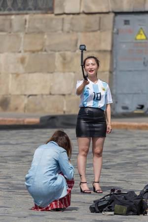 Junge Frau mit Maradona-Trikot schießt ein Selfie