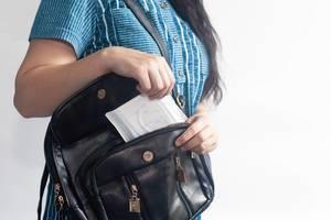 Junge Frau packt für die Menstruationstage eine Damenbinde in ihre Handtasche ein