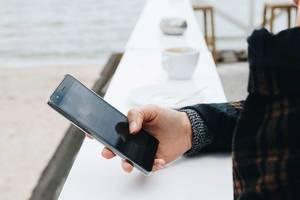 Junge Frau verwendet draußen ein Smartphone