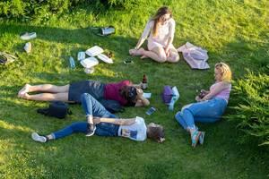 Junge Frauen liegen auf dem Rasen in einem Park in Moskau
