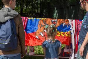 Junge Fußballfans schauen sich Flaggen und Schals an