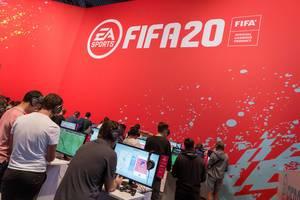 Junge Gamer spielen FIFA 20 von EA Sports an Spielstationen auf der Gamescom