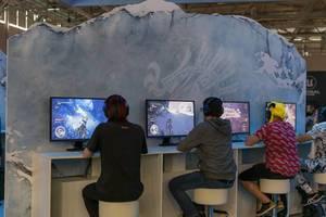 Junge Gamescombesucher spielen das Action-Rollenspiel Monster Hunter World: Iceborne von Capcom