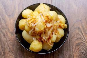 Junge, gekochte Kartoffeln mit frischen Zwiebeln in einer schwarzen Schüssel auf dunklem Holz