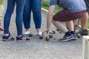 Junge Männer und Frauen spielen Boule