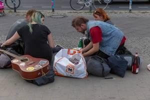 Junge Menschen mit Gitarre sitzen auf dem Gehsteig