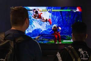 Junge Messebesucher zocken Videospiel im Zweispieler-Modus, auf einem Panasonic-Bildschirm
