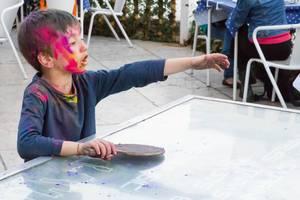 Junge mit Holi-Farbe spielt Tischtennis