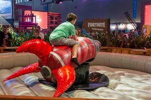 Junge reitet eine Rakete am Messestand von Fortnite auf der Gamescom