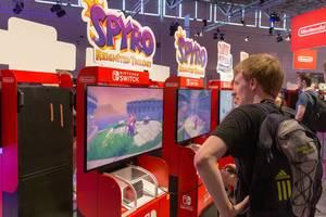 Junge Spielemesserbesucher der Gamescom spielen Spyro - Reignited Trilogy auf der Nintendo Switch
