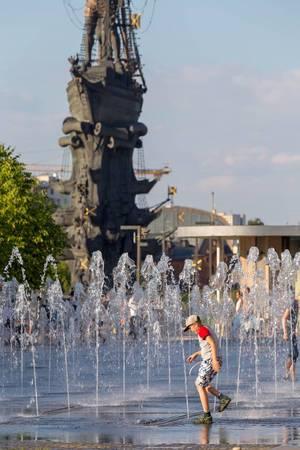 Junge spielt im Springbrunnen unweit des Denkmals für Peter I.