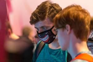 Junge trägt Mundschutz-Maske mit Gebissaufdruck, auf der Gamescom