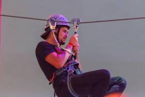 Junger Mann auf einer Seilrutsche