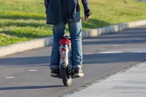 Junger Mann fährt auf einem elektrischen Einrad