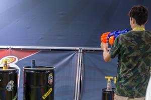 Junger Mann im Begriff mit einem Blaster mit Schaumstoffmunition zu schießen