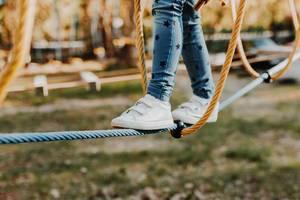 Junges Mädchen geht am Seil im Seilpark. Fokus auf die Füße