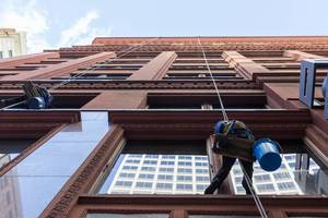 Just attached to a rope: professional window cleaners working on the outside of a building in Chicago