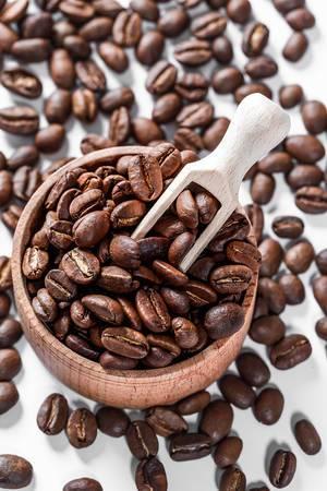 Kaffeebohnen in einer Holzschale mit Holzkelle