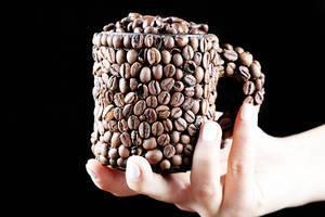 Kaffeebohnen Tasse in einer Frauenhand