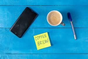 Kaffeepause mit einer vollen Tasse, Handy und einem Stift, auf einem blauen Tisch