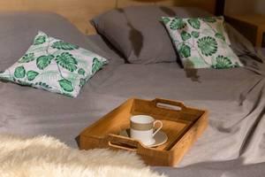 Kaffeetasse für Frühstückskaffee auf Holztablett steht auf Bett mit bunten Kissen und Fell