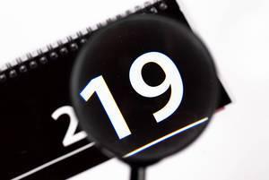 Kalender 2019 betrachtet durch Leselupe vor weißem Hintergrund