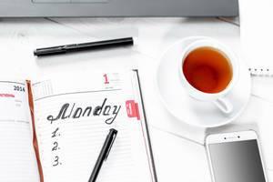 Kalenderbuch mit vorbereiteter To-Do-Liste und Schreiber, einer Tasse Tee und weißem Smartphone