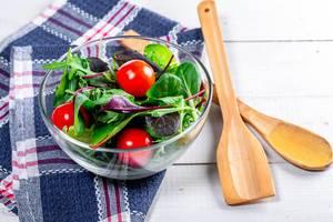 Kalorienarmer Salat mit frischen Tomaten und Kräutern in einer Glasschale auf blauem Küchentuch neben Holzbesteck