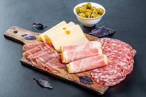 Kalte Platte mit Wurst- und Käsespezialitäten sowie grüne Oliven auf schwarzem Hintergrund